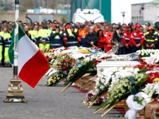 An Italian flag waves next to a row of coffins during the funerals for quake victims in L'Aquila, central Italy, Friday, April 10, 2009. (AP / Luca Bruno)