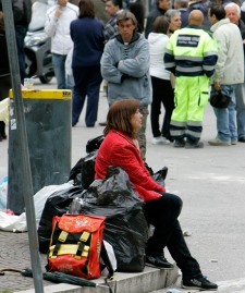 A woman sits on her personal belongings in garbage bags in downtown L'Aquila, central Italy, after a retrieval operation for quake victims, Saturday April 11, 2009. (AP / Antonio Calanni)