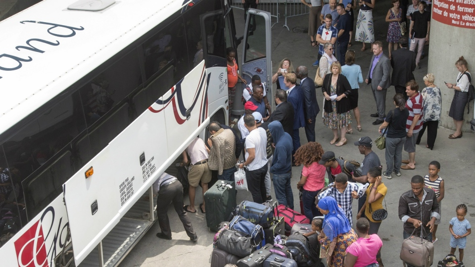 A busload of asylum seekers arrives at Olympic Stadium in Montreal on Thursday, Aug. 3, 2017. (Ryan Remiorz / THE CANADIAN PRESS)