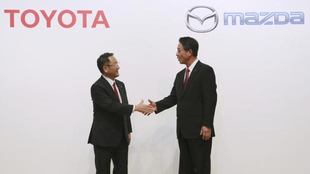 Akio Toyoda, left, and Masamichi Kogai shake hands