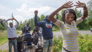 A group of asylum seekers raise their hands as they approach RCMP officers while crossing the Canadian border Friday, August 4, 2017 in Champlain, N.Y. (Ryan Remiorz/The Canadian Press)