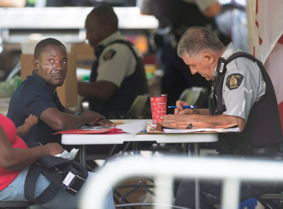 An asylum seeker is processed by RCMP officers after crossing the border into Canada from Champlain, N.Y., in Hemmingford, Que., Friday, August 4, 2017. (Ryan Remiorz/The Canadian Press)