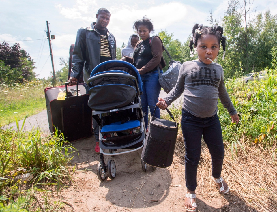 A group of asylum seekers crosses the Canadian border Friday, August 4, 2017 in Champlain, N.Y. (Ryan Remiorz/The Canadian Press)