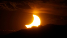 In this May 20, 2012, file photo, the annular solar eclipse is seen as the sun sets behind the Rocky Mountains from downtown Denver. (AP Photo/David Zalubowski, File)