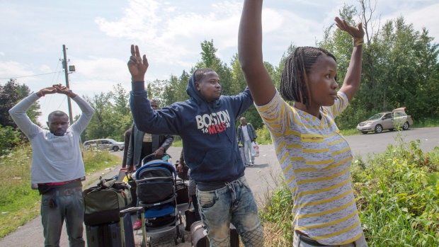 A group of asylum seekers raise their hands as they approach RCMP officers while crossing the Canadian border at Champlain, N.Y., Friday, August 4, 2017.THE CANADIAN PRESS/Ryan Remiorz