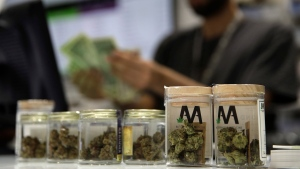 FILE - In this July 1, 2017 file photo, a cashier rings up a marijuana sale at the Essence cannabis dispensary in Las Vegas. (AP Photo/John Locher)