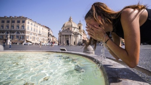 A woman cools off in a fountain at Piazza del Popolo in Rome, Italy, Thursday, Aug. 3, 2017. (Angelo Carconi/ANSA via AP)