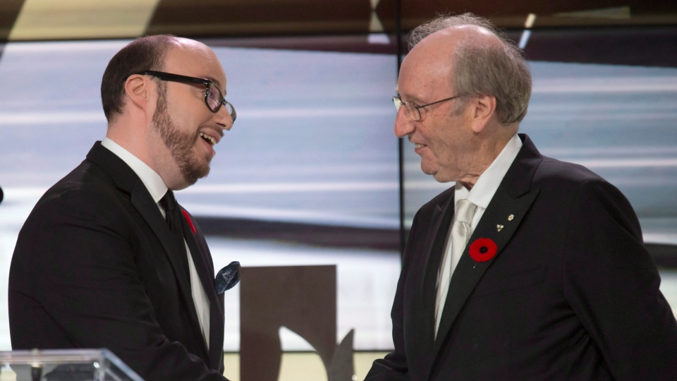 "Sean Michaels (left) shakes hands with Giller Prize founder Jack Rabinovitch after winning the Giller Prize for his book ""Us Conductors"" at the awards ceremony in Toronto on Monday November 10, 2014. (THE CANADIAN PRESS/Frank Gunn)"