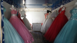 Bridal gowns and engagement dresses are displayed in a small shop in the Zaatari camp for Syrian refugees in northern Jordan on Sunday, Aug. 6, 2017. (AP / Reem Saad)