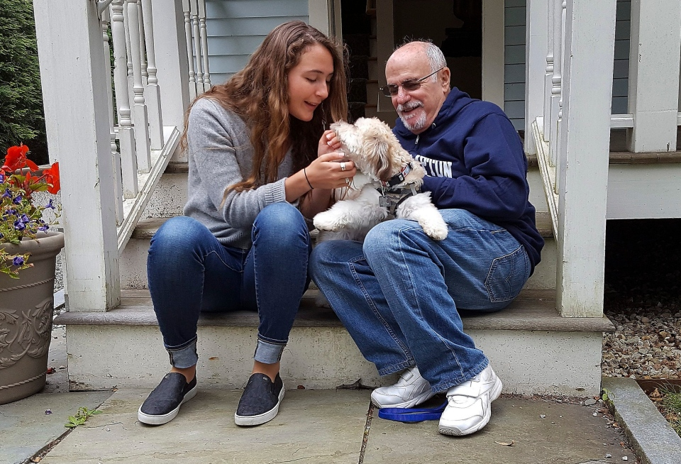 In this photo provided by the Boston Symphony Orchestra, Grace Ellrodt, left, and conductor David Zinman sit with Zinman's puppy Carlito outside his home Monday, Aug. 7, 2017, in Lenox, Mass. (Hilary Scott/Boston Symphony Orchestra via AP)