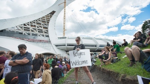 People hold up signs in support of asylum seekers during a rally outside the Olympic Stadium in Montreal, Sunday, Aug. 6, 2017. (Graham Hughes / THE CANADIAN PRESS)