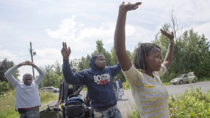 A group of asylum seekers raise their hands as they approach RCMP officers while crossing the Canadian border at Champlain, N.Y., on Aug. 4, 2017. (Ryan Remiorz / THE CANADIAN PRESS)