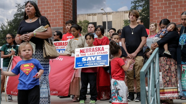 An unidentified child wears a Superman shirt in front of members of native American tribes who were holding a prayer during a rally outside the building where the Nebraska Public Service Commission was holding a hearing on the fate of the Keystone XL pipeline, in Lincoln, Neb., Tuesday, Aug. 8, 2017. (AP Photo/Nati Harnik)