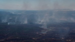 Smoke from wildfires fills the air and burned trees are seen in this aerial view from a Canadian Forces Chinook helicopter near Williams Lake, B.C., on Monday, July 31, 2017. THE CANADIAN PRESS/Darryl Dyck