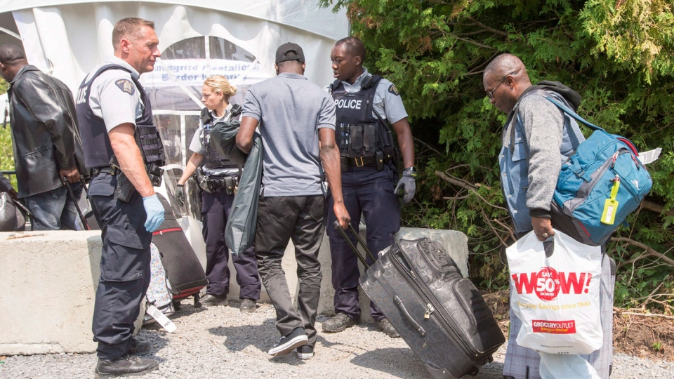 A group of asylum seekers cross the Canadian border at Champlain, N.Y., Friday, August 4, 2017. (Ryan Remiorz / THE CANADIAN PRESS)