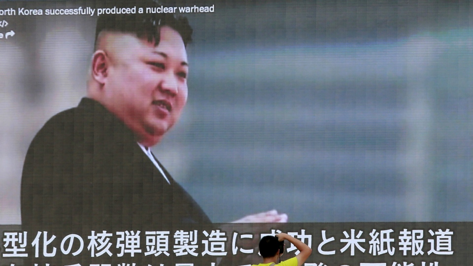 A man takes a photo of a TV news program showing an image of North Korean leader Kim Jong Un while reporting North Korea's rocket launch in Tokyo on Wednesday, Aug. 9, 2017. (AP / Shizuo Kambayashi)