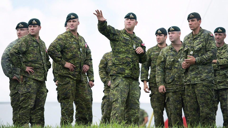 Members of the Canadian armed forces look around onsite where they will be erecting tents to house asylum seekers at the Canada-United States border in Lacolle, Que. Wednesday, August 9, 2017. (Graham Hughes/THE CANADIAN PRESS)