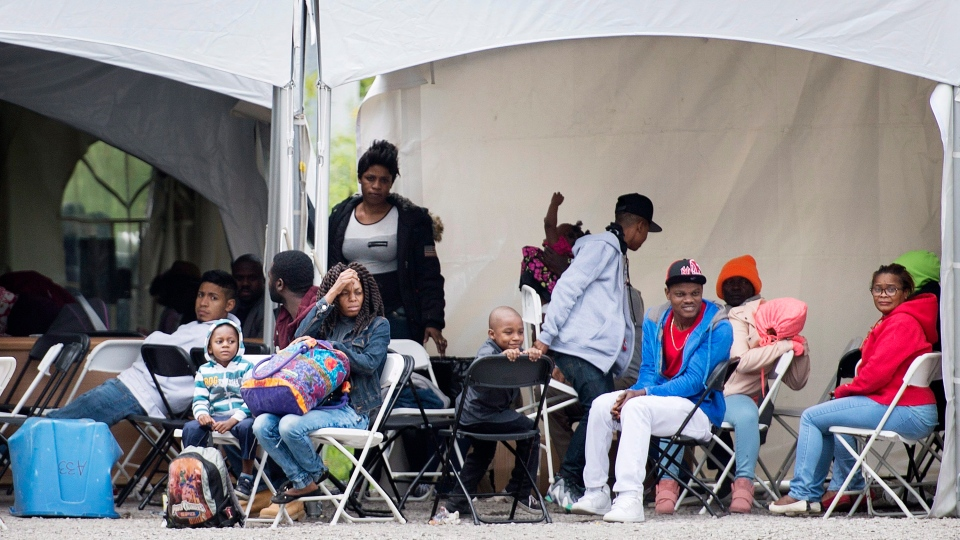 Asylum seekers wait to be transported to a processing centre after entering Canada illegally from the United States at Roxham road in Hemmingford, Que. on Aug. 9, 2017. (Graham Hughes / THE CANADIAN PRESS)