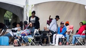 Asylum seekers wait to be transported to a processing centre after entering Canada illegally from the United States at Roxham road in Hemmingford, Que., Wednesday, Aug. 9, 2017. (Graham Hughes / THE CANADIAN PRESS)