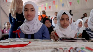 Syrian refugees pose for a photo during a visit by U.N. Secretary General Antonio Guterres to a fourth-grade classroom at the U.N.-run Zaatari camp for Syrian refugees, in northern Jordan in this March 28, 2017 file photo. A growing number of Syrian child brides and refugee kids skipping school to work are among the tangible impacts of the three billion dollar gap between the financial needs of Syrian refugees in the Middle East and the funds available to pay for them. (AP Photo / Raad Adayleh)