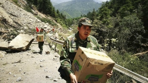 Chinese paramilitary policemen carry boxes of supplies past a section of road blocked by a landslide after an earthquake in Jiuzhaigou county in southwestern China's Sichuan province on Wednesday, Aug. 9, 2017. (Chinatopix)