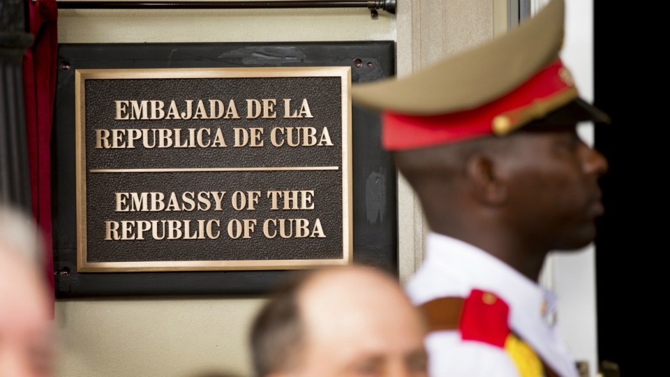 A member of the Cuban honour guard stands next to a new plaque at the front door of the newly reopened Cuban embassy in Washington on July 20, 2015. (AP / Andrew Harnik)