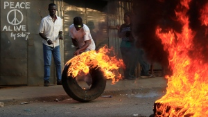 Residents of Kibera in Nairobi, Kenya, roll a burning tire as they blocked the main street to protest in support of Kenyan opposition leader and presidential candidate Raila Odinga, Wednesday Aug. 9, 2017. (AP Photo/Noor Khamis)