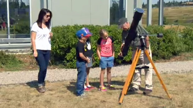 Melanie Hall, and Alan Dyer help a group of children look through a telescope outside TELUS Spark