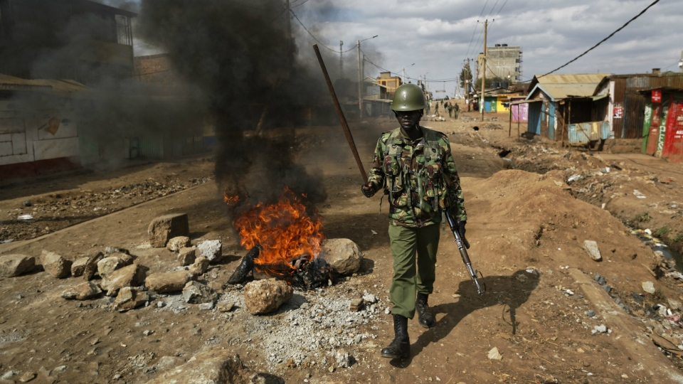 A riot policeman walks past burning barricades erected by protesters throwing rocks, during clashes in the Kawangware slum of Nairobi, Kenya on Thursday, Aug. 10, 2017. (AP / Ben Curtis)