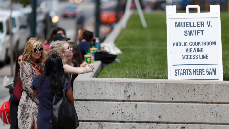 Members of the public line up to get a pass to attend the afternoon session of a civil trial for pop singer Taylor Swift, Thursday, Aug. 10, 2017, in Denver. (AP Photo/David Zalubowski)