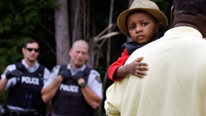 A Haitian boy holds onto his father as they approach an illegally crossing point, staffed by Royal Canadian Mounted Police officers, from Champlain, N.Y., to Saint-Bernard-de-Lacolle, Quebec, Monday, Aug. 7, 2017.  (AP / Charles Krupa)