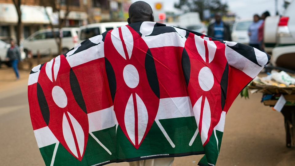 A supporters of President Uluru Kenyatta walks with a Kenyan flag in anticipation of the announcement of the presidential election's final results Friday, Aug. 11, 2017, in Kikuyu Town, Kenya. (AP / Jerome Delay)