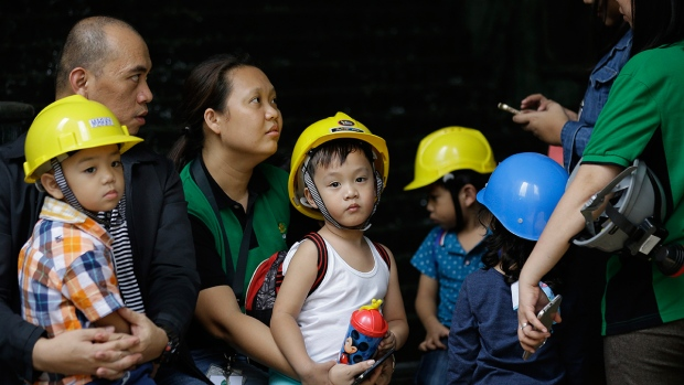 Children wear helmets as they evacuate a building after an earthquake was felt in Manila, Philippines on Friday, Aug. 11, 2017. (AP / Aaron Favila)
