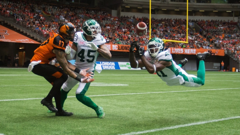 Saskatchewan Roughriders' Ed Gainey, right, dives and nearly intercepts a pass intended for B.C. Lions' Nick Moore, left, as Saskatchewan's Kacy Rodgers II (45) watches during the second half of a CFL football game in Vancouver, B.C., on Saturday August 5, 2017. THE CANADIAN PRESS/Darryl Dyck