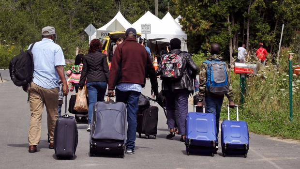 A family from Haiti approach a tent in Saint-Bernard-de-Lacolle, Quebec, stationed by Royal Canadian Mounted Police, as they haul their luggage down Roxham Road in Champlain, N.Y., Monday, Aug. 7, 2017. (AP Photo/Charles Krupa)