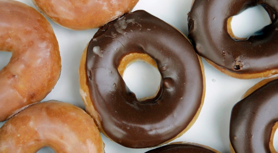 In this April 17, 2008, file photo, Krispy Kreme doughnuts are shown in Matthews, N.C. Krispy Kreme announced Aug. 9, 2017, that it's giving its signature glazed treats a chocolate sheen for the first time ever in honor of the Aug. 21 eclipse. (AP Photo / Chuck Burton, File)