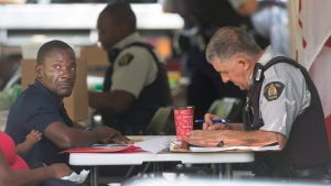 An asylum seeker is processed by RCMP officers after crossing the border into Canada from Champlain, N.Y., in Hemmingford, Que., Friday, August 4, 2017. (Ryan Remiorz / THE CANADIAN PRESS)