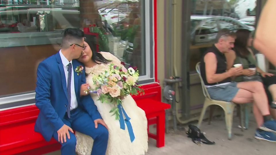 Newlyweds Aaron and Andrea de Guzmans share a kiss in front of the Drake Hotel on Aug. 11, 2017. (CTV Toronto)