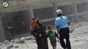 This photo provided by the Syrian Civil Defense group known as the White Helmets, shows civilians rushing out of the damaged buildings after airstrikes hit a school housing a number of displaced people, in the western part of the southern Daraa province of Syria, June 14, 2017. (Syrian Civil Defense White Helmets via AP)