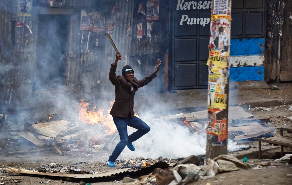 "A man brandishing a ""panga"" machete challenges police next to a burning barricade during clashes between police and protesters in the Mathare slum of Nairobi, Kenya Saturday, Aug. 12, 2017. (Ben Curtis/AP Photo)"