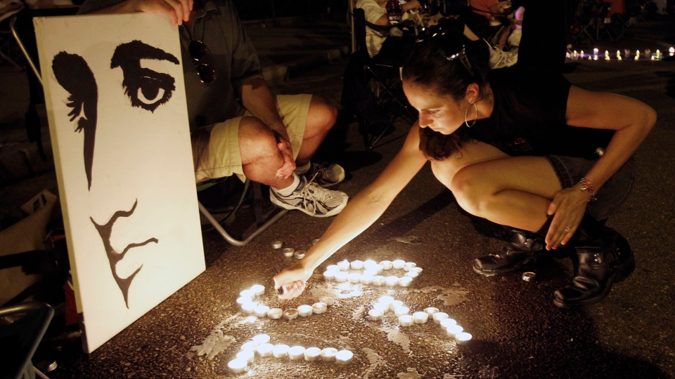 This Aug. 15, 2010 file photo shows Melanie Curry as she lights candles at an Elvis Presley display she made with Judd Cannon, left, on Elvis Presley Boulevard in front of Graceland, Presley's Memphis, Tenn. home. (Mark Humphrey/AP)