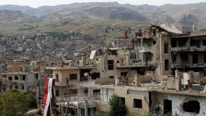 In this May 18, 2017 file photo, a Syrian National flag hangs out of a damaged building at the mountain resort town of Zabadani in the Damascus countryside, Syria. (AP Photo/Hassan Ammar, File)