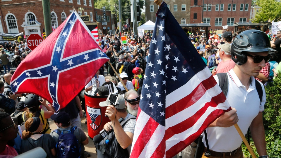 White nationalist demonstrators walk into Lee park surrounded by counter demonstrators in Charlottesville, Va., Saturday, Aug. 12, 2017. (Steve Helber/AP)
