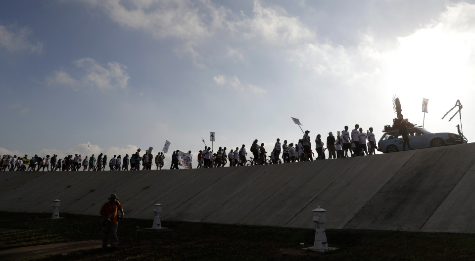 Hundreds of people march along a levee in South Texas toward the Rio Grande to oppose the wall the U.S. government wants to build on the river separating Texas and Mexico, Saturday, Aug. 12, 2017, in Mission, Texas. The area would be the target of new barrier construction under the Trump administration's current plan. (Eric Gay/AP Photo)