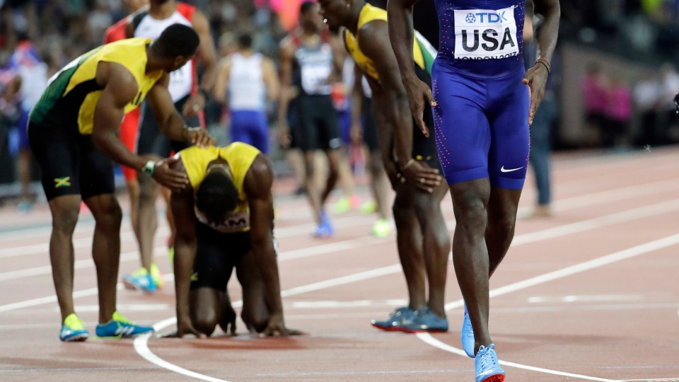 Justin Gatlin of the United States' walks away after checking on Jamaica's Usain Bolt, second left, who is assisted by his teammates after he pulled up injured in the final of the Men's 4x100m relay during the World Athletics Championships in London Saturday, Aug. 12, 2017. (AP Photo / David J. Phillip)
