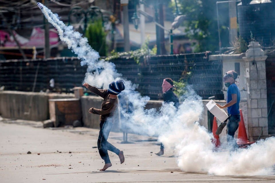 A Kashmiri protester throws back an exploded tear gas shell at Indian police in Srinagar, Indian controlled Kashmir, Friday, Aug. 11, 2017. (Dar Yasin/AP Photo)
