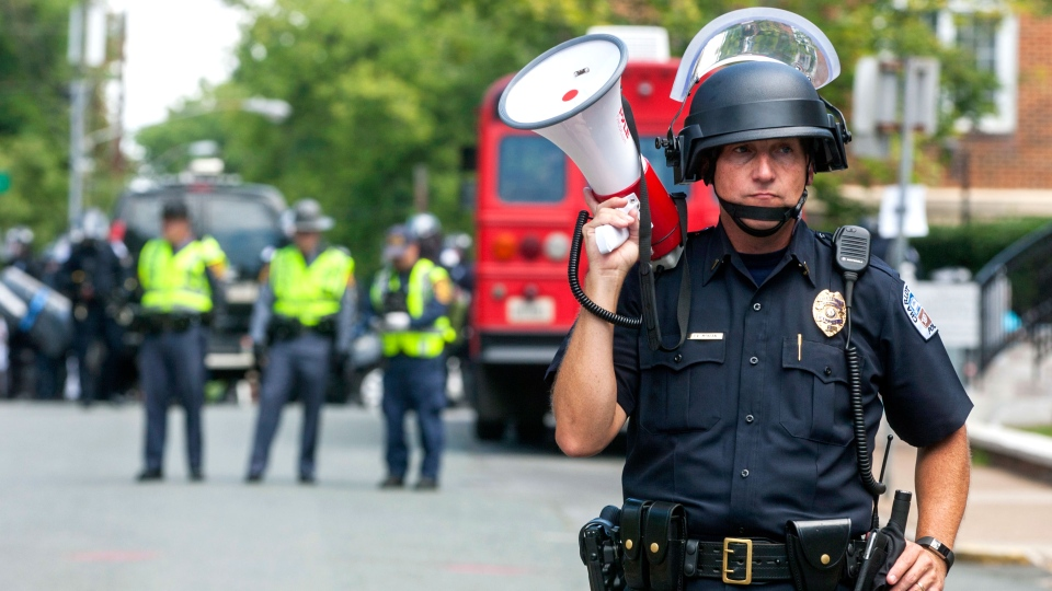 A police officer stands in the middle of the street after declaring the protest an unlawful assembly during a white nationalist rally, on Saturday Aug. 12, 2017, in Charlottesville, Va. (Shaban Athuman/Richmond Times-Dispatch via AP)