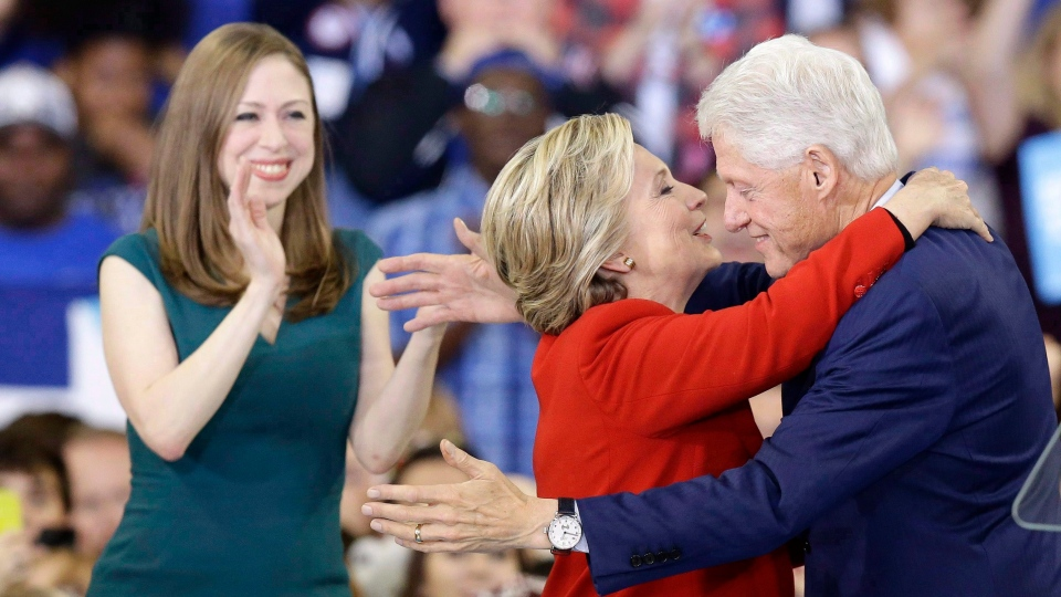 Former Democratic presidential candidate Hillary Clinton hugs her husband, former President Bill Clinton as their daughter Chelsea Clinton looks on during a campaign rally in Raleigh, N.C., Tuesday, Nov. 8, 2016. (Gerry Broome/AP/The Canadian Press)