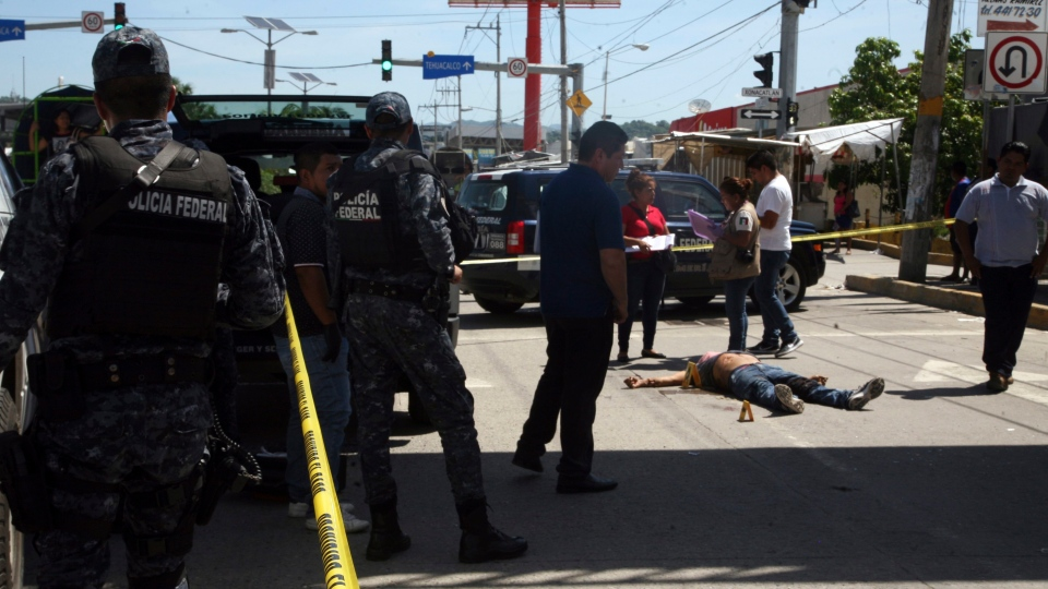 Federal police tape off the area where a man who was shot dead in broad daylight on a central avenue in Acapulco, Mexico, Sunday, Aug. 13, 2017. At least four people were shot dead in Acapulco Sunday, as Mexico recently recorded its highest monthly murder total in at least 20 years. (AP Photo/Bernandino Hernandez)