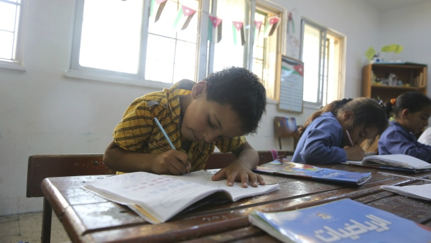 A Syrian refugee boy takes notes during a lesson at a summer school in Amman, Jordan on Thursday, July 20, 2017. (AP / Reem Saad)